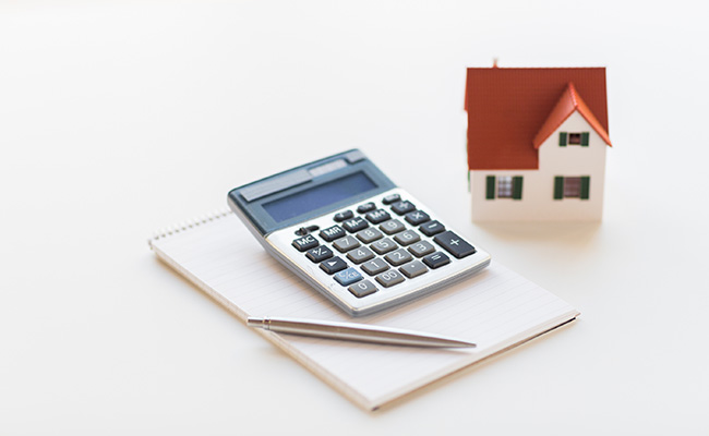 building, mortgage, real estate and property concept - close up of home model, house keys and notebook with pen