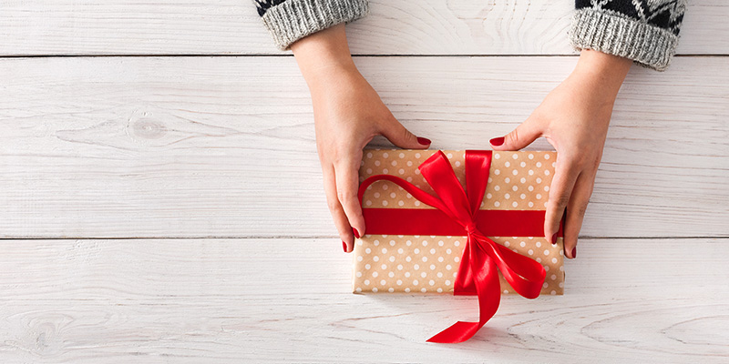 DIY hobby. Woman's hands wrapping christmas or other holiday handmade present in paper with red ribbon. Give present box, decoration of gift on white wooden table, top view with copy space
