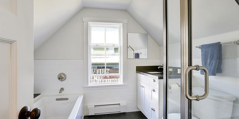 Modern white bathroom interior in the attic. The room has vaulted ceiling view of glass shower door bathroom vanity with black top and bathtub. Northwest USA