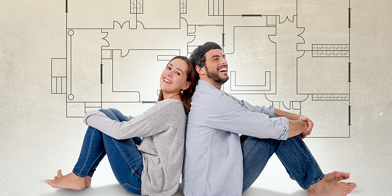 Young attractive couple in love happy together thinking and imaging blueprints floor plan and design of new house home flat or apartment in real state concept