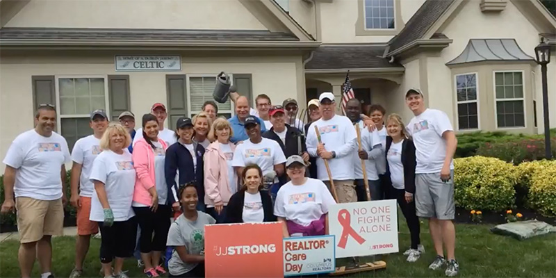 Group of realtors posing outside home - Realtor Care Day